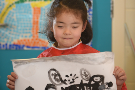 A young child holding up a picture she has drawn of her family
