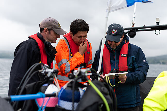 Three scientists on a boat looking at a clipboard