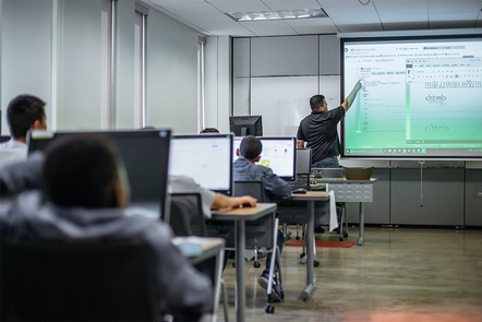 A photograph of a computer science classroom and teacher