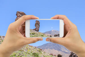 A person holds a smartphone up to take a picture of a landscape scene.