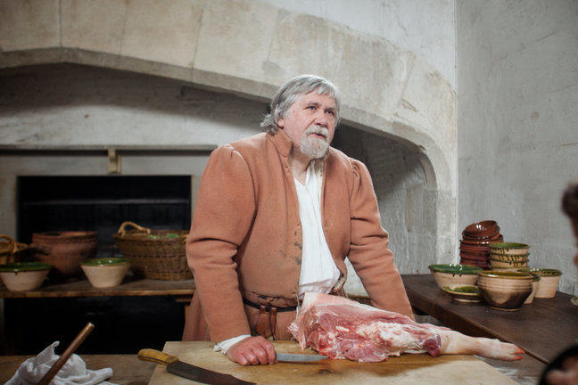 A photograph of a reenactment in a kitchen, with a cook standing next to a leg of pork.