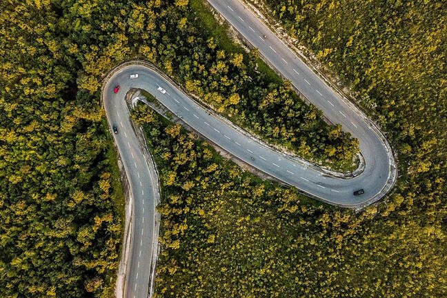 Aerial shot of a winding road through woodland