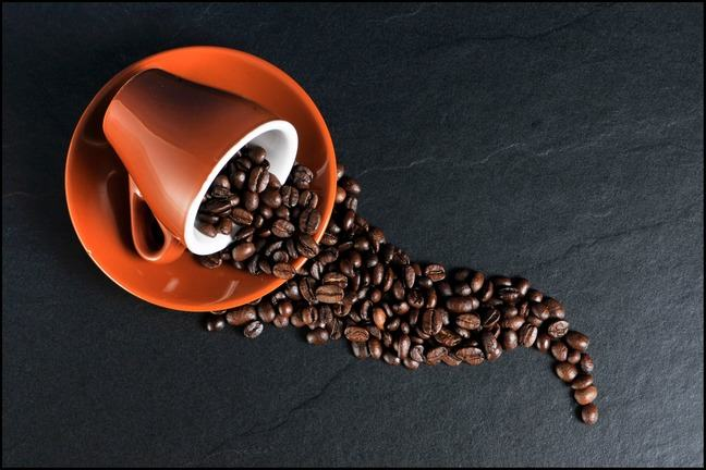 Coffee cup on its slide with beans spread across a surface.