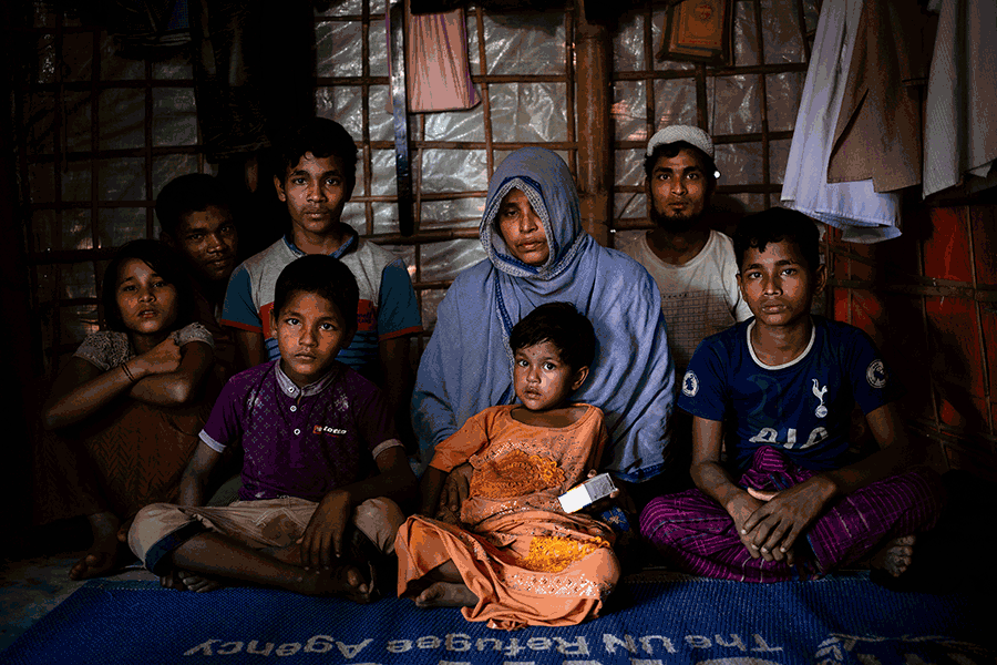 A family of eight sits on a blue UNHCR mat against a wooden wall covered with plastic. Scattered pieces of clothing hang from the walls. The youngest child sitting in the middle holds a box of medicine.