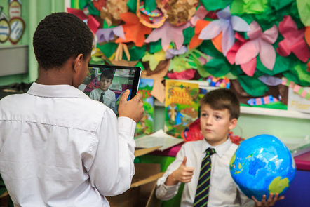 Two boys in a classroom filming with an iPad