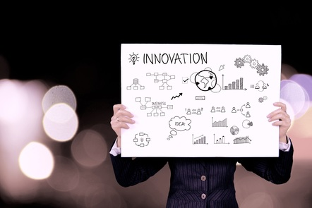 Man holding a large sheet of paper, with the word 'Innovation' and various diagrams and cycles drawn on it.