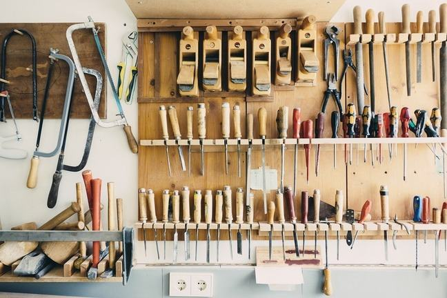 A selection of carpentry tools hanging on the wall of a wooden workshop.