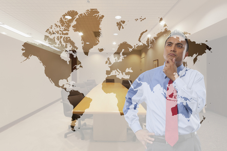 A business man contemplates a world map displayed on a screen in front of him.