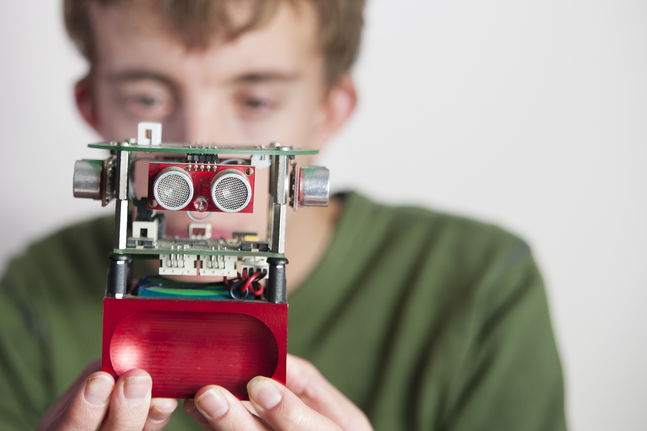 A student holding a small robot at the University of Reading