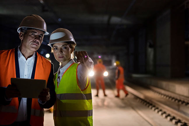 Female engineer instructing a foreman at a rail site, night scene.