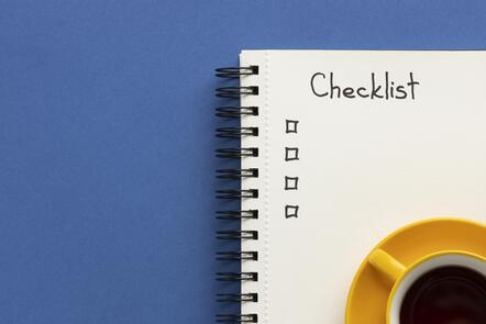 A notebook with a checklist of items lies on a blue desk alongside of a cup of coffee