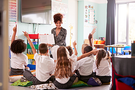 Children with raised hands in the classroom