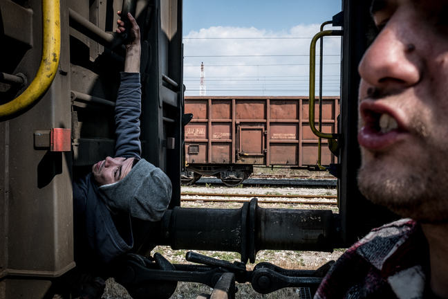 Two unaccompanied teenage boys are hanging from a moving train, trying to find a way to hold on and hide to allow them to cross borders.