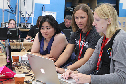 A photograph of a group of educators working together on a coding project