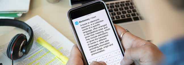Man holding phone that shows definition of the word 'dictionary'