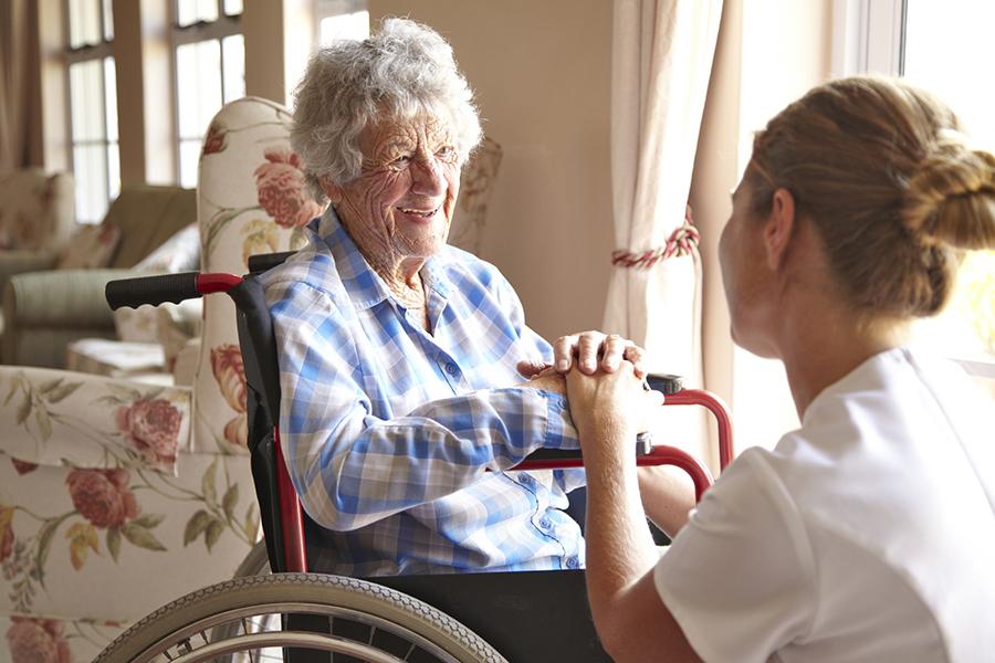 Elderly woman talking to a nurse in a retirement home