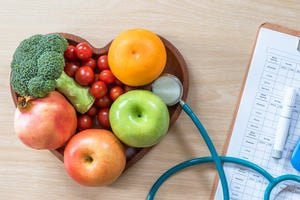 Heart-shaped wooden bowl full of fruit. Sitting on a wooden table next to a stethoscope.
