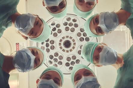 doctors and nurses looking down at a camera