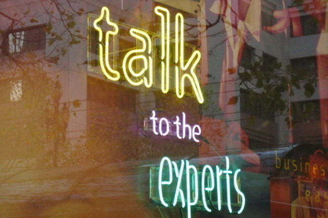 "The words ""Talk to the experts"" in neon lights"