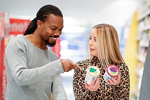 A man and a woman are choosing between two tubs of icecream in a supermarket. The man is pointing at the label of one and the woman is looking at him questioningly.