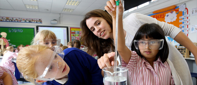 School girls and a teacher conduct a science experiment.