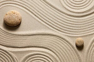 Image of Zen garden with swirling sand patterns around rocks.  This image represents a free online course on Mindfulness for Wellbeing and Peak Performance.