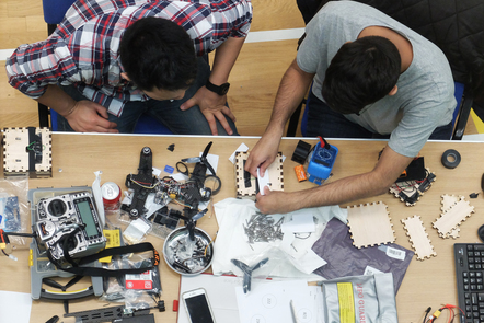 Two students work with mechanical parts of a drone hackathon.