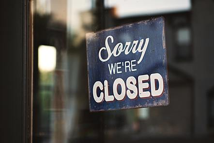 A photograph of a sign in a shop window which reads 'Sorry we're closed'.