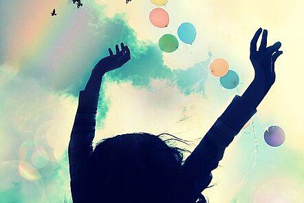 La imagen muestra lo que parece ser una niña levantando los brazos hacia el cielo. Hay globos con colores que se asemejan a los del arco iris, que también está presente en el cielo. La imagen también muestra pájaros volando.