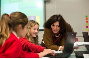 A female teacher leans over to look at a laptop, while two female students are both reaching for its keyboard