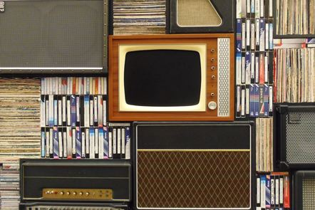 A television on shelves with vinyl and VHS collections
