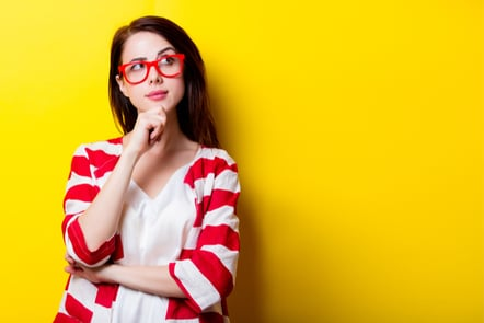 A young woman thinking with red glasses and a cardigan on.