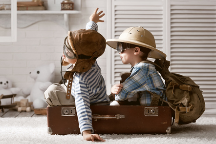 Two children playing and pretending they're going on their holidays to explore.