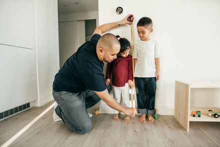 father measuring height of son and daughter