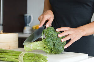 Person cutting green vegetables