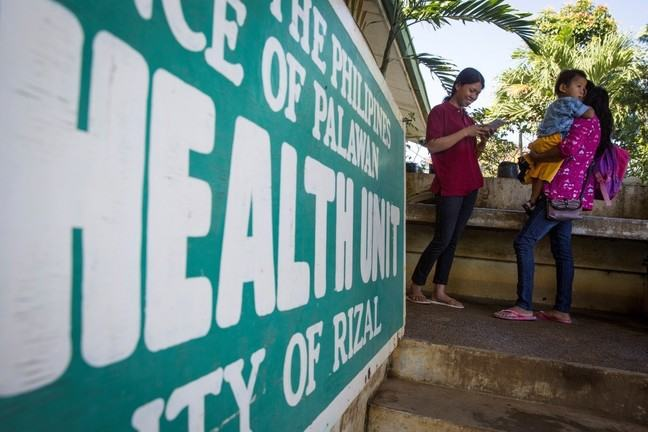 Two mothers and a child stand outside of a health unit in the Philippines