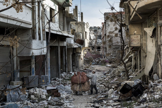 Photograph of a man pushing a trolley amidst rubble in Homs