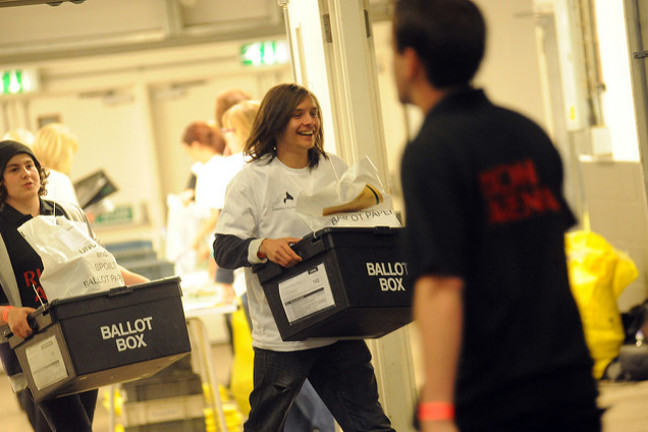 Election Volunteers Carrying Ballot Boxes Full of Votes on Election Night at a Counting Station