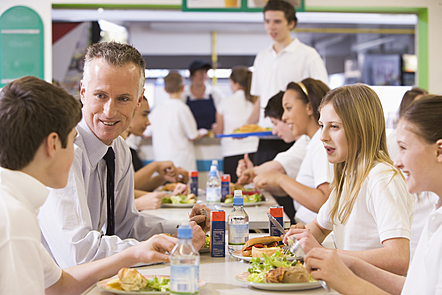 A teacher eating lunch with his students in the school cafeteria