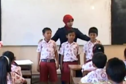 A teacher in Indonesia stands behind 3 students as she demonstrates how to compare heights