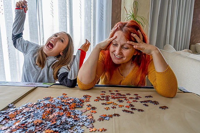 An adult and young person doing a jigsaw together and smiling