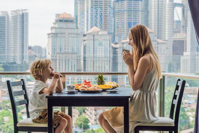 People eating food on balcony.