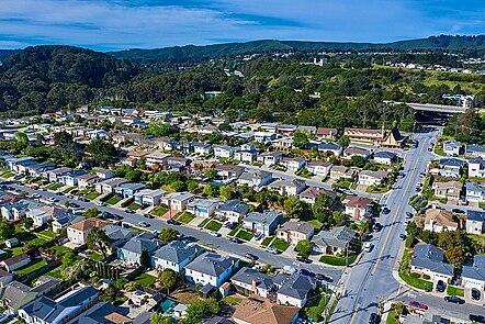 La imagen muestra la vista aérea de un vecindario en California. Las casas tienen pasto verde en sus jardines delanteros y se ven muchos árboles. Parece ser un día tranquilo, ya que muchos de los autos están estacionados y no se ven personas.