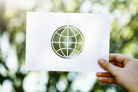Picture of a globe being held up over a leafy background