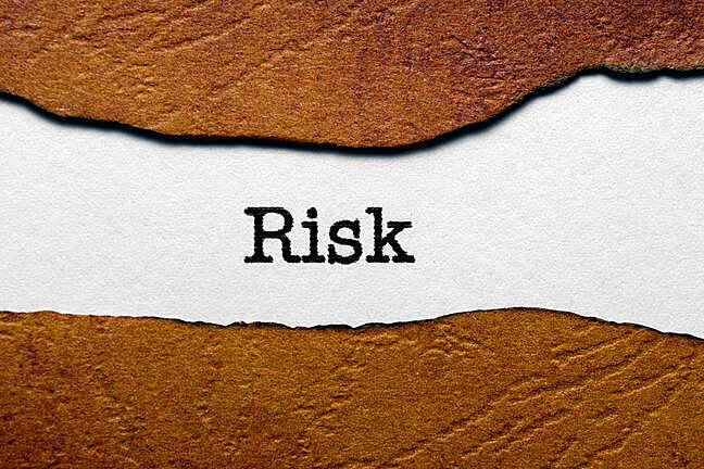 The word 'Risk' written in a white background with a brown frame