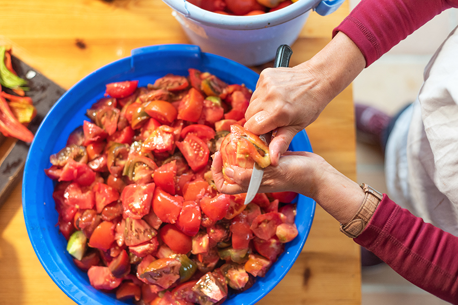 Woman cutting large amount of tomatoes for prepare tomato sauce. Preparation of tomatoes for cooking.