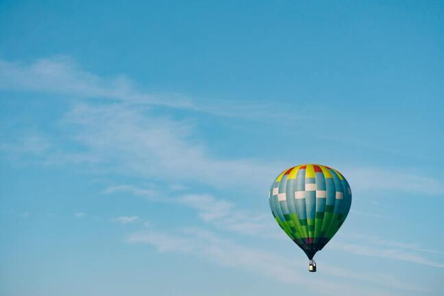 A photograph of a colourful air balloon floating against a cloudless blue sky by Aaron Burden.