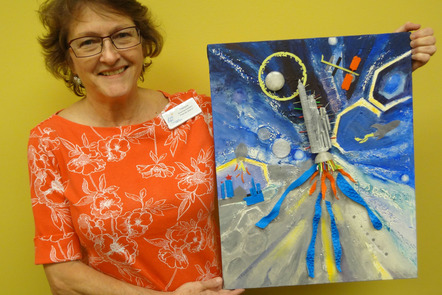 A woman holding a multimedia painting of a rocket