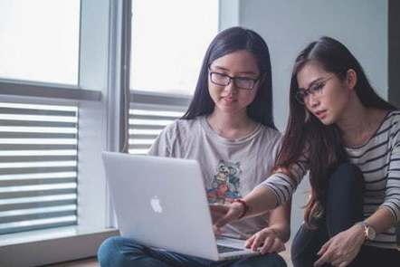 2 young ladies working on a computer