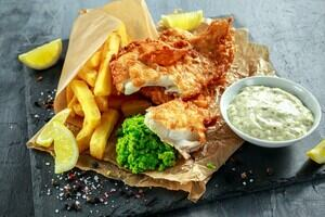A serving of fish and chips, with peas